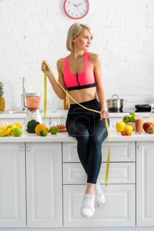 Photo for Attractive girl in sportswear holding measuring tape near ingredients in kitchen - Royalty Free Image