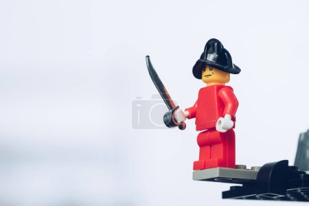 Photo for KYIV, UKRAINE - MARCH 15, 2019: red lego pirate figure in hat holding sword on white with copy space - Royalty Free Image