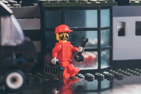kyiv, Ukraine - 15. März 2019: rote Lego-Arbeiterfigur mit Hut, Schraubenschlüssel und Werkzeugkiste in der Nähe eines Gebäudes aus Legosteinen