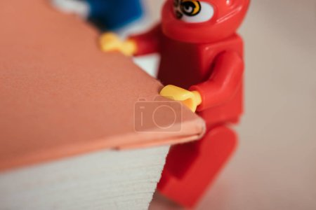Photo for KYIV, UKRAINE - MARCH 15, 2019: close up view of red lego minifigure carrying book - Royalty Free Image