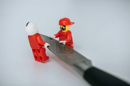 Photo for KYIV, UKRAINE - MARCH 15, 2019: red lego figurines carrying metal knife on white - Royalty Free Image