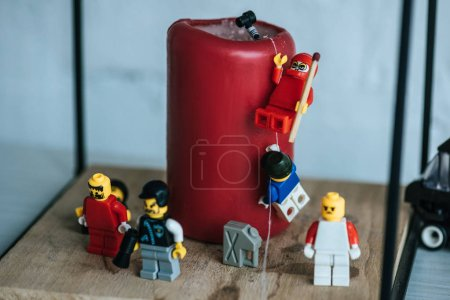 Photo for KYIV, UKRAINE - MARCH 15, 2019: close up view of lego characters climbing red candle with rope - Royalty Free Image
