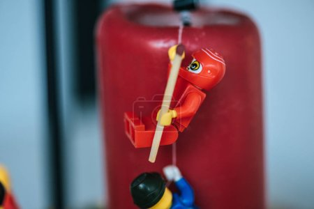 Photo for KYIV, UKRAINE - MARCH 15, 2019: close up view of plastic red lego figurine with match climbing candle with rope - Royalty Free Image