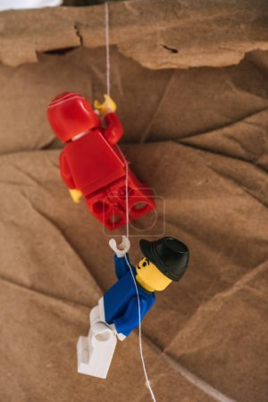 Photo for KYIV, UKRAINE - MARCH 15, 2019: close up view of red and blue plastic lego figurines climbing rope - Royalty Free Image