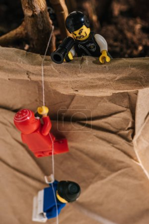 Photo for KYIV, UKRAINE - MARCH 15, 2019: plastic lego figurines climbing rope while toy policeman yelling in mouthpiece - Royalty Free Image