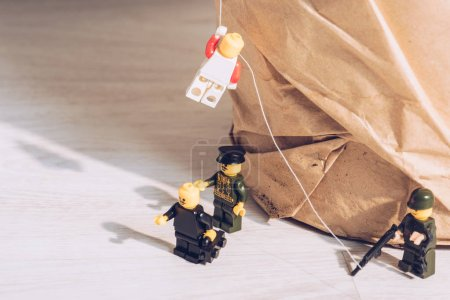 Photo for KYIV, UKRAINE - MARCH 15, 2019: toy policemen standing with weapon while plastic lego figurine climbing rope - Royalty Free Image