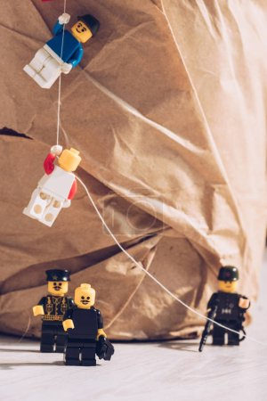 Photo for KYIV, UKRAINE - MARCH 15, 2019: lego policemen standing with weapon while plastic lego figurines climbing rope - Royalty Free Image