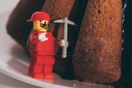 Photo for KYIV, UKRAINE - MARCH 15, 2019: close up view of plastic lego figurine with toy icebreaker near cake - Royalty Free Image