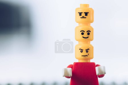 Photo for KYIV, UKRAINE - MARCH 15, 2019: red lego figurine with indifferent, smiley and angry faces on heads on white with copy space - Royalty Free Image