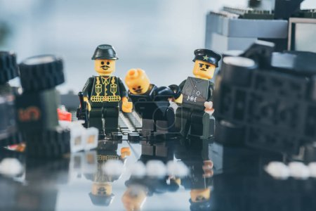 Photo for KYIV, UKRAINE - MARCH 15, 2019: Selective Focus of policemen figurines in uniform and hats arresting lego figure in black - Royalty Free Image