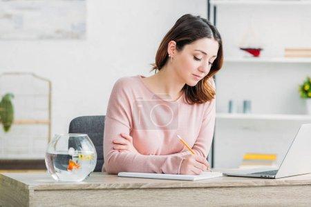 Photo pour Attrayant femme concentrée écrivant dans le cahier tout assis à la table à la maison - image libre de droit