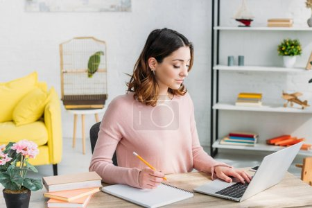 Photo for Beautiful attentive woman working at home while sitting at home with laptop - Royalty Free Image