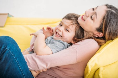 Photo for Happy mother with cheerful son resting on yellow sofa at home - Royalty Free Image