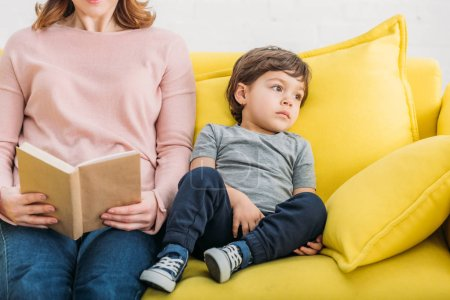 Photo for Partial view of woman reading book near adorable son resting on sofa at home - Royalty Free Image
