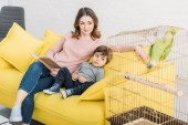 """Постер, картина, фотообои """"улыбаясь мать с очаровательны сын сидит на диване рядом с птичьим возрастом с зеленым попугаем"""""""