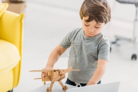 adorable boy playing with wooden plane model at home