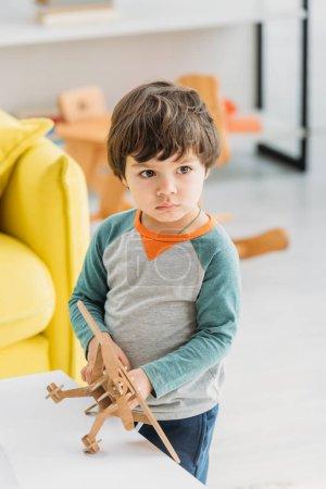 adorable enfant sérieux tenant modèle d'avion en bois à la maison