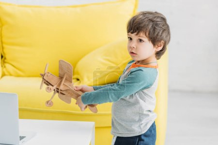 Photo for Cute boy playing with wooden plane model near sofa at home - Royalty Free Image