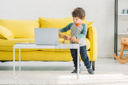 Photo for Adorable child playing with wooden plane model near laptop at home - Royalty Free Image