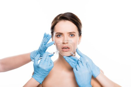 Photo for Cropped view of cosmetologists in latex gloves touching face of shocked girl while holding  syringes isolated on white - Royalty Free Image