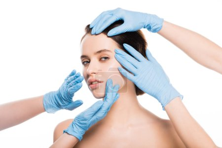 Photo for Cropped view of plastic surgeons in blue latex gloves touching face of naked girl looking at camera isolated on white - Royalty Free Image