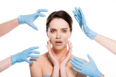 Photo for Cropped view of plastic surgeons in blue latex gloves near face of surprised girl isolated on white - Royalty Free Image