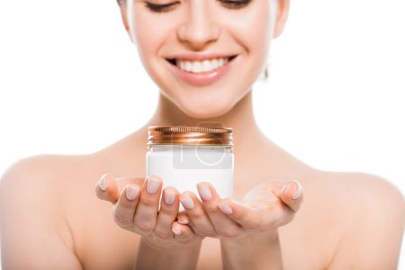 cropped view of naked young woman holding container with face cream and smiling isolated on white
