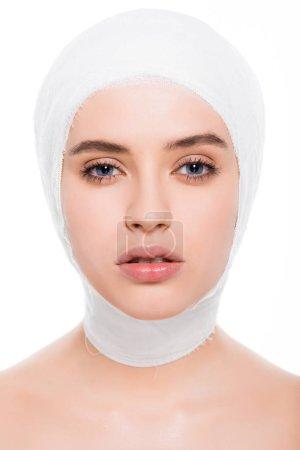 Photo pour Jeune femme attirante avec la tête bandée regardant la caméra isolée sur le blanc - image libre de droit