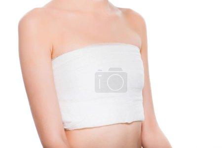 Photo pour Vue recadrée de la jeune femme avec le sein bandé après la chirurgie plastique d'isolement sur le blanc - image libre de droit