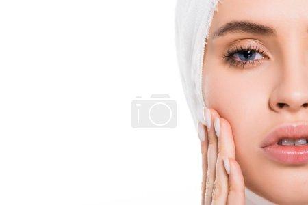 Photo pour Vue recadrée de la jeune femme avec la tête bandée touchant le visage après la chirurgie plastique d'isolement sur le blanc - image libre de droit