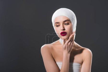 Photo pour Jeune femme attirante avec la tête de bandée touchant le visage isolé sur le gris - image libre de droit