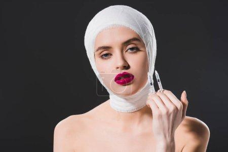 Photo pour Femme assez jeune avec la tête bandée retenant des seringues isolées sur le gris - image libre de droit