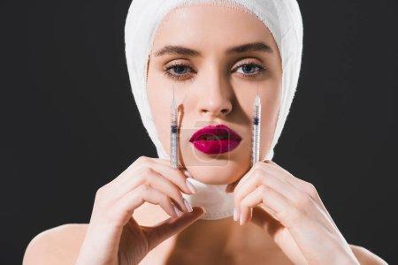 Photo pour Jeune femme attirante avec les seringues de fixation de tête bandée près du visage isolé sur le gris - image libre de droit