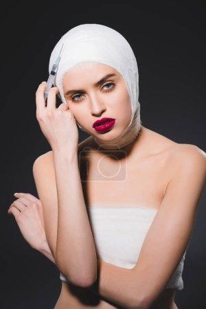 Photo pour Belle femme avec la tête bandée retenant la seringue d'isolement sur le gris - image libre de droit