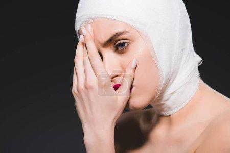Photo pour Jeune femme avec le visage de couverture de tête bandée isolé sur le gris - image libre de droit