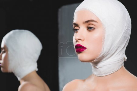 Photo for Mirror reflection of attractive young woman with bandaged head on grey - Royalty Free Image