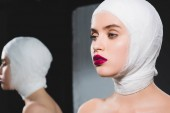 mirror reflection of attractive young woman with bandaged head on grey