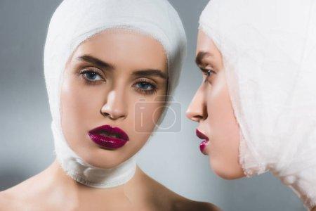 Photo pour Reflet miroir de la jeune femme belle avec la tête bandée sur le gris - image libre de droit