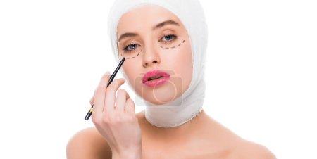 Photo pour Photo panoramique de la jeune femme avec des marques sur le visage et bandée tête tenant stylo marqueur isolé sur fond blanc - image libre de droit