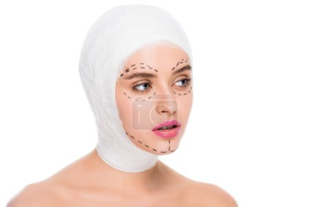 Foto de Nude pretty young woman with bandaged head and marks on face isolated on white - Imagen libre de derechos