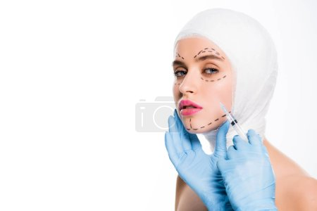 Photo for Cropped view of plastic surgeon in latex gloves holding syringe near face of young woman with marks isolated on white - Royalty Free Image
