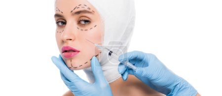 Photo pour Panoramic shot of plastic surgeon in latex gloves holding syringe near face of young woman with marks isolated on white - image libre de droit