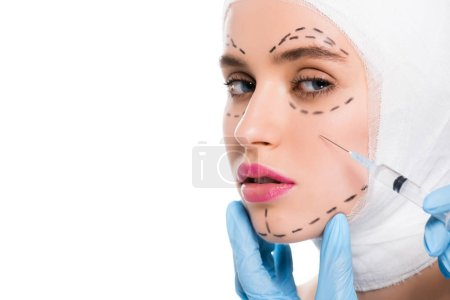 Photo pour Cropped view of plastic surgeon in latex gloves holding syringe near face of woman with marks isolated on white - image libre de droit