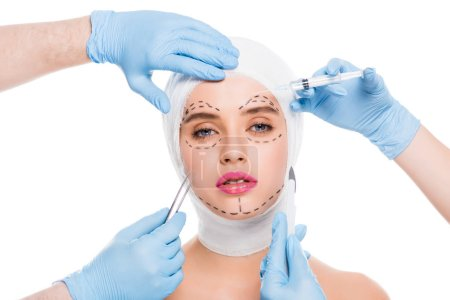 Photo pour Cropped view of plastic surgeons in blue latex gloves with medical equipment near face of woman with marks isolated on white - image libre de droit