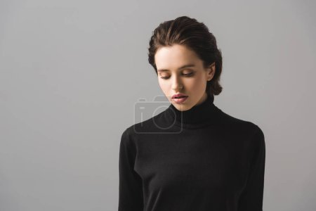young woman in black jumper isolated on grey