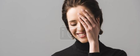 panoramic shot of cheerful young woman in black jumper covering eye isolated on grey