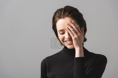 cheerful young woman in black jumper covering eye isolated on grey