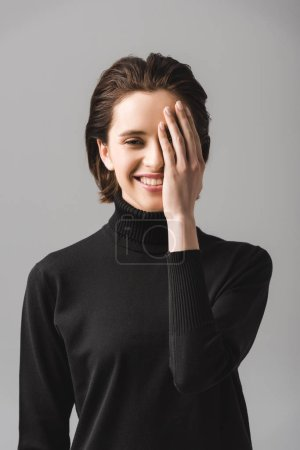 Photo for Happy young woman in black jumper covering eye isolated on grey - Royalty Free Image