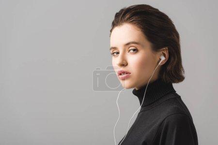 Photo pour Jeune femme en pull noir écoutant de la musique dans des écouteurs isolés sur gris - image libre de droit