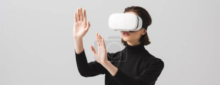 Photo for Panoramic shot of brunette young woman wearing virtual reality headset while gesturing isolated on grey - Royalty Free Image